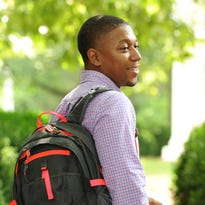 Clemson MBA student Matt Brown wears an LED device on his backpack that lets cyclists signal turns from the handlebars.