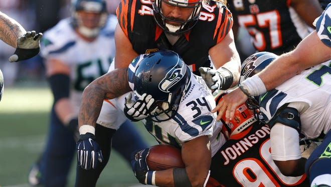 Seattle Seahawks running back Thomas Rawls (34) is tackled by Cincinnati Bengals defensive end Michael Johnson (90) and defensive tackle Domata Peko (94) in overtime of an NFL football game, Sunday, Oct. 11, 2015, in Cincinnati. The Bengals won 27-24.