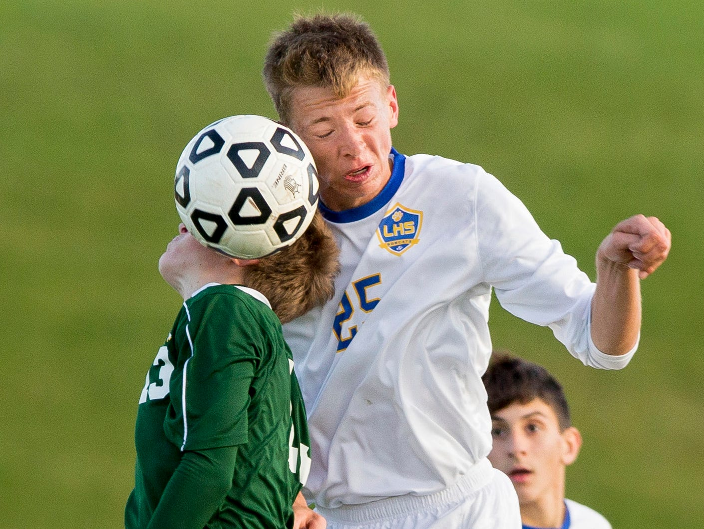 Greene's Spencer Klumpp, left, and Lansing's Karsten Zuidema fight for the ball as Lansing's Kyle Button, background watches Thursday during Lansing's 2-1 overtime win in the Section 4 Class C semifinals at Lansing.