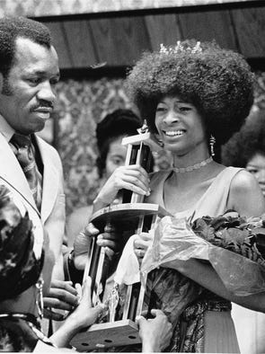 Beverly Thompson, who reigned over the first Indiana Black Expo in 1971, accepted a gleaming trophy and a dozen roses from James C. Cummings Jr. (left) after defeating 22 other candidates in the Miss Black Indiana contest