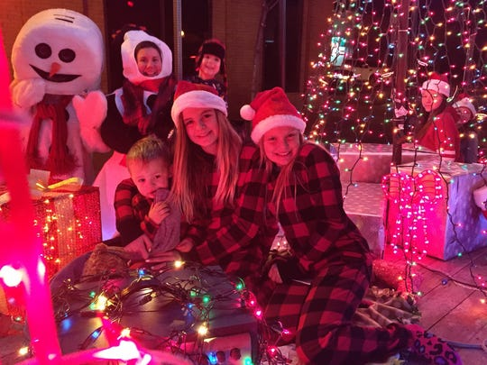 Thurston, Holland and Srb families ride in the Park Place Healthcare Christmas morning float at the Parade of Lights downtown Saturday.
