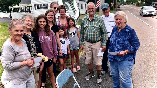 """Family members of triplets Nancy Bourdeau, left, her brother Neil Pineo, third from right, and sister Norma Pineo, right, are seen here in Raynham after a """"birthday parade"""" had driven past to celebrate the triplets' 80th birthday."""