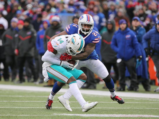 Bills Leonard Johnson wraps up dolphins receiver Jarvis Landry after a short gain.