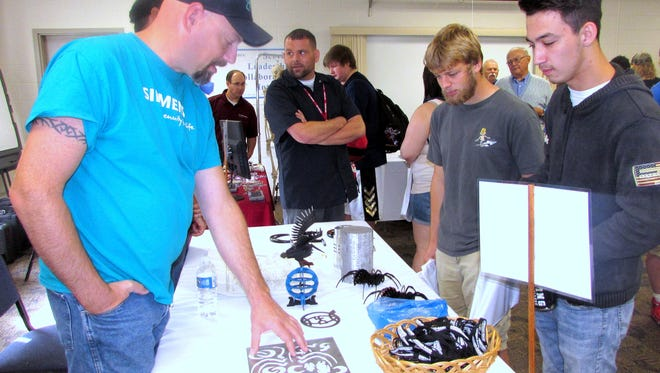 Dresser-Rand representative Jerry Smith, left, shows off some of the company's products to students Zachary Tsaklis, right, and Troy Wilhelm during Friday's Made in Chemung Manufacturing Day.