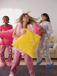 Three girls jumping at slumber party