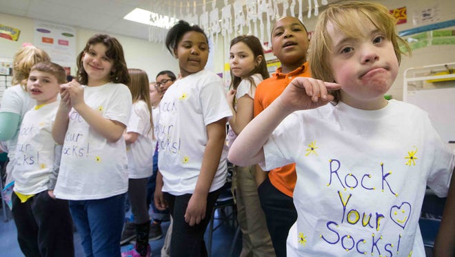 """Claymont Elementary School students on Friday stand behind classmate Aaron Janusz, who has Down syndrome, and sing """"You've Got a Friend in Me."""" Saturday is World Down Syndrome Awareness Day, and events were held at schools throughout Delaware on Friday."""