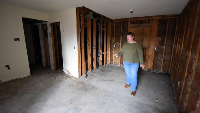 Kathy Garner, executive director at AIDS Service Coalition, looks in one of the empty apartment rooms at Sheley Place.