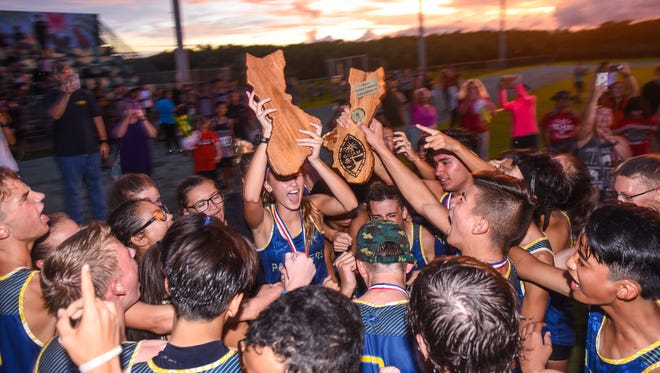 The Guam High School Panthers' cross country team celebrate with their trophies winning the boys and girls championships during the Independent Interscholastic Athletic Association Cross Country League All-Island cross country meet at John. F. Kennedy High School on Thursday, Oct. 5, 2017. Both the school's girls and the boys teams remained undefeated thoughout the season while competing against other island high schools.