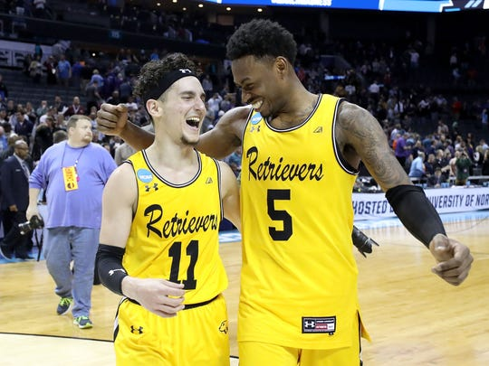 K.J. Maura and Jourdan Grant of the UMBC Retrievers celebrate their 74-54 victory over the Virginia Cavaliers.
