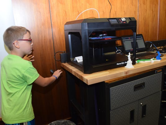 ANI TREE House 3-D printer at Library Owen Edwards looks to see what the 3-D printer at the Rapides Parish Library in downtown Alexandria is making. He is a camper at the T.R.E.E. House Children's Museum's science camp being held this week.-Melinda Martine