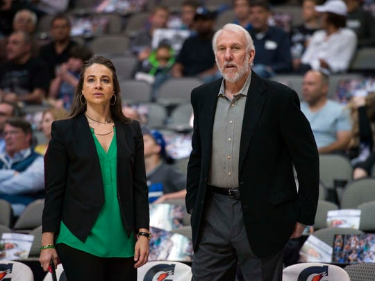 San Antonio Spurs coaches Becky Hammon and Gregg Popovich watch their team warm up before a game against the Dallas Mavericks.