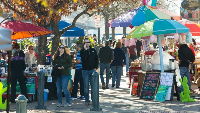 People wander through downtown Las Cruces during the Farmers and Crafts Market in 2016. The city is seeking funds to design a parking garage for downtown.