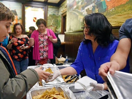 Julie Torres serves empanadas at the first-ever First