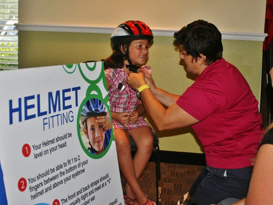 Clara Saez, 5, gets fitted for a bicycle helmet during Thursday's backpack day organized by Lehigh Community Services. Lisa Indovino of Safe Routes To School Lee County helped children find the right helmet.
