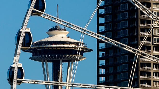 The Space Needle peeks from between the pods of Seattle's Great Wheel.