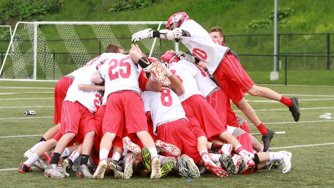 The Champlain Valley Union High School Redhawks leap into a championship pile in celebration of their 2014 Division I state final win Saturday against South Burlington.