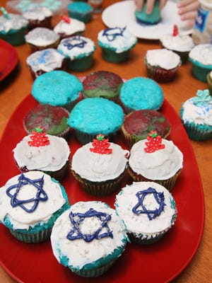 Cupcakes — blue for Hanukkah and red and green for Christmas — are decorated for both holidays.