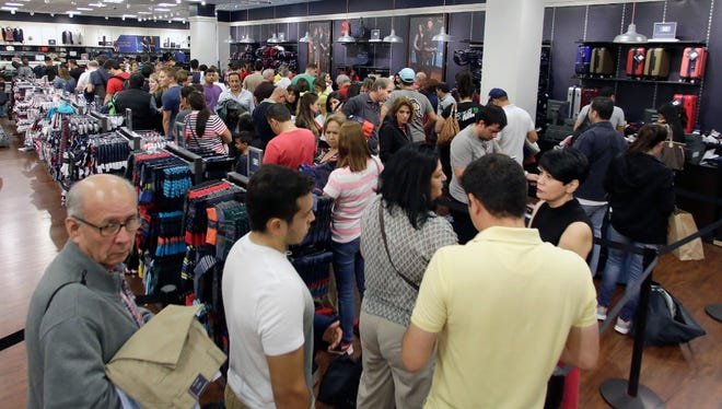 Shoppers stand in line to pay for their purchased merchandise at a Tommy Hilfiger in Miami on Black Friday.