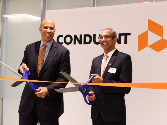 Ashok Vemuri, chief executive officer, and U.S. Sen. Cory Booker cut the ribbon at the official opening of Conduent headquarters, a provider of business process services, in Florham Park, New Jersey, on June 2, 2017.