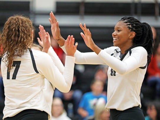 Ankeny Centennial middle hitter Devyn Robinson (11), right, celebrates a point with teammates.