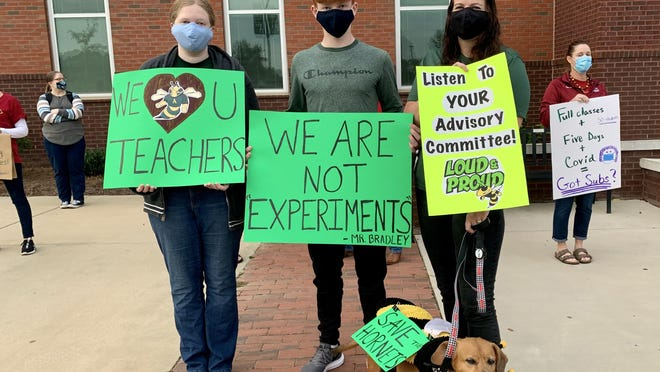 Aiken High School color guard director Melody Brinkley, right, protests the school board's decision to return hybrid students to full in-person learning outside Aiken High Friday, Oct. 9 with her daughter Eva, left, her son William, center, and their furry-friend Punkin, bottom.