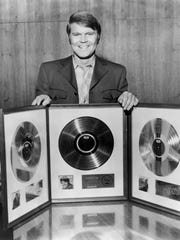 Glen Campbell with three gold and platinum records