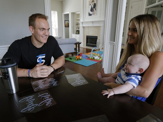 Former NFL fullback and creator of the Ice Shaker water bottle and shaker cup, Chris Gronkowski, sits with his wife, Brittany, and son, Bear, as the two pause from working at their home, in Colleyville, Texas.