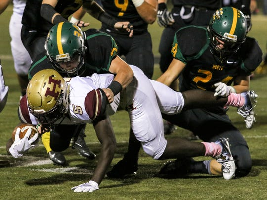Hillsborough's Charles Amankwaa is brought down by North Hunterdon's Kyle Hensler (34) and Erik Dehkes (24) during the first half on Friday, Oct. 20, 2017 at North Hunterdon.