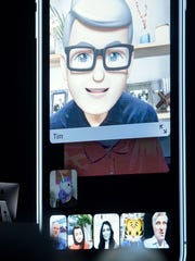 Apple CEO Tim Cook, top , speaks using his Memoji during a group FaceTime call on stage during Apple's Worldwide Developer Conference at the San Jose Convention Center in San Jose, Calif. on June 4, 2018.