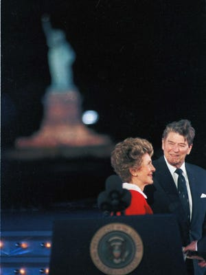 President Ronald Reagan smiles at his wife, first lady Nancy Reagan, after he lit up the Statue of Liberty, left background, during the official unveiling ceremony on New York's Governor's Island on July 3, 1986. [Ira Schwarz/The Associated Press[