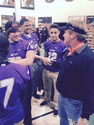 Jon Gruden talks with players from Green Bay West.