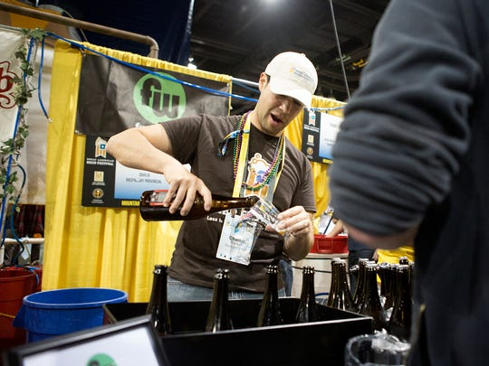 Charles Barker of Funkwerks pours beer for Patrons at the 2014 Great American Beer Festival.