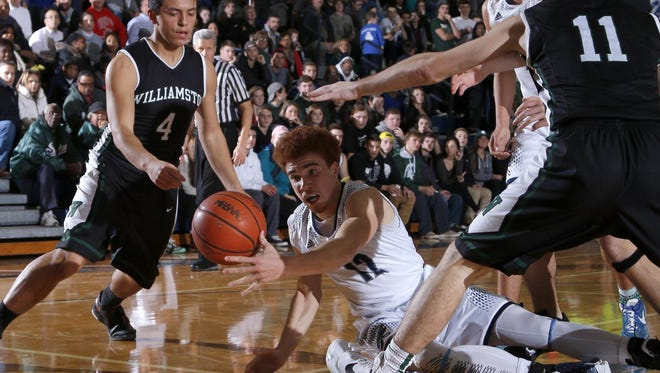East Lansing's DeAndre Robinson, center, and Williamston's Frankie Toomey (4) and Connor Porrell (11) fight for a loose ball Tuesday. Robinson had 19 points to help East Lansing to a 78-37 win.