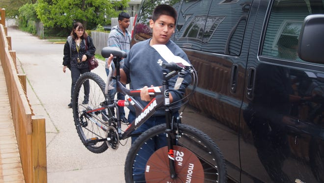 Joe Ramirez, a student at St. Lawrence Seminary High School in Mount Calvary, loads up a new bicycle for delivery to children living in temporary shelters run by Solutions Center in Fond du Lac.