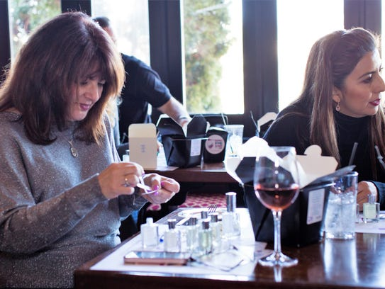 Women enjoy creating their own scents at a recent Invent