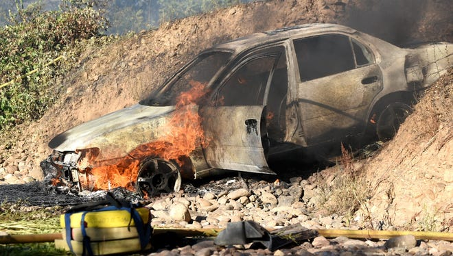 Flames burn a car off Canyon Road on Saturday evening that led to a fire going uphill south of Redding.