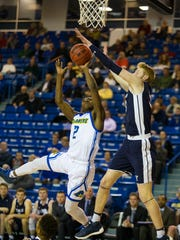 The University of Delaware's Ryan Allen (2) attempts a layup against Yale's Blake Reynolds (32) Monday night at the Bob Carpenter Center. UD lost to Yale 76-66.