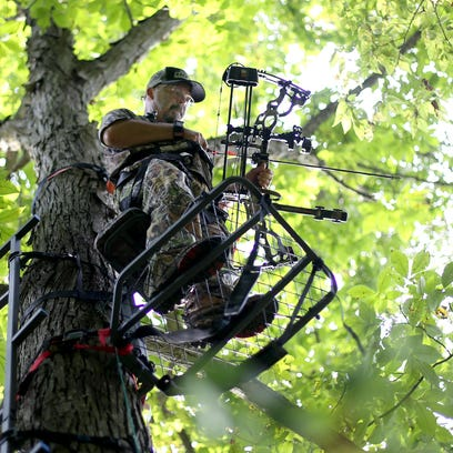 Dave Cash stands in a tree stand in the backyard of