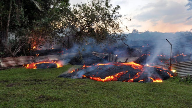 This Tuesday, Oct. 28, 2014 photo provided by the U.S. Geological Survey shows lava that has pushed through a fence marking a property boundary above the town of Pahoa on the Big Island of Hawaii. After weeks of slow, stop-and-go movement, a river of asphalt-black lava was less than the length of a football field from homes in the Big Island community Tuesday.