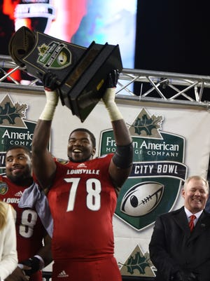 Louisville offensive tackle Aaron Epps (78) holds up the  Franklin American Mortgage Music City Bowl trophy after Louisville beat Texas A&M 27-21 at Nissan Stadium Wednesday Dec. 30, 2015, in Nashville, Tenn.