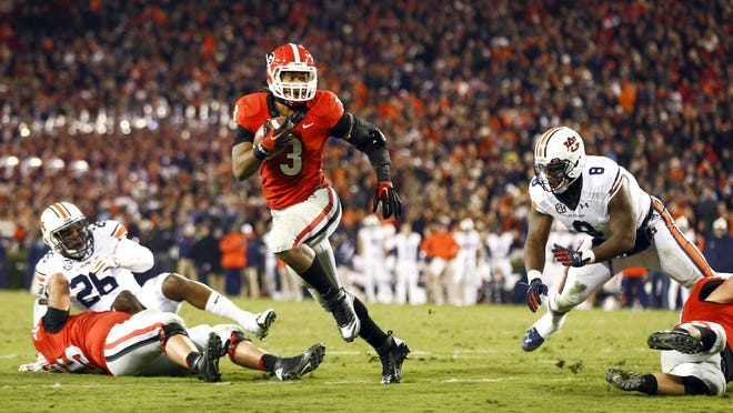 Georgia running back Todd Gurley (3) runs between Auburn linebacker Justin Garrett (26) and Auburn linebacker Cassanova McKinzy (8) to score a touchdown in the second half of an NCAA college football game Saturday, Nov. 15, 2014, in Athens, Ga.