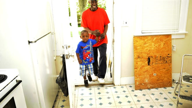 "Veteran Bobby Kirkland, top, who was homeless living in Oakland County, walks into his new home in Pontiac with his son, Ja-Boree Kirkland, 4. ""I would like to eventually purchase a home but for now, this is very nice. I'm grateful,"" Kirkland said."