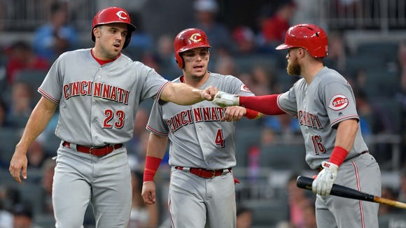 Aug 19, 2017; Atlanta, GA, USA; Cincinnati Reds left fielder Adam Duvall (23) and second baseman Scooter Gennett (4) react with on deck batter catcher Tucker Barnhart (16) after scoring against the Atlanta Braves during the fourth inning at SunTrust Park.