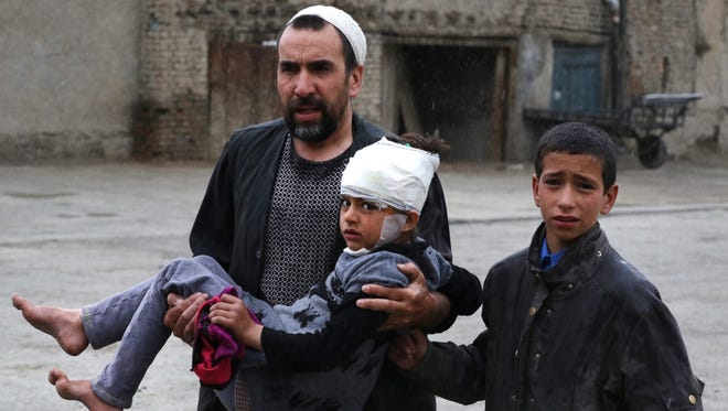 An Afghan man carries a girl who was injured in a suicide bomb blast that targeted the premises of the Ministry of Defense, in Kabul, Afghanistan, April 19, 2016.
