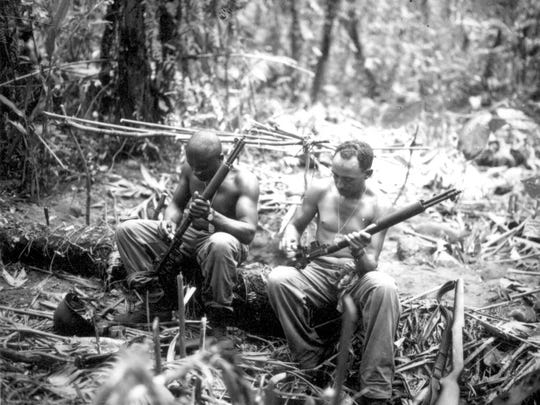 Sgt. John C. Clark and S/Sgt. Ford M. Shaw (left to right) clean their rifles in a bivouac area alongside the East West Trail, Bougainville, on April 4, 1944. They were members of Co. E, 25th Combat Team, 93rd Division.