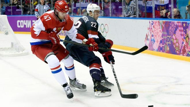 USA defenseman and New Rochelle native Kevin Shattenkirk, right, keeps the puck away from Russia forward Alexander Radulov at the Sochi Olympics on Saturday. Shattenkirk assisted on the goal that gave Team USA a 2-1 third-period lead.