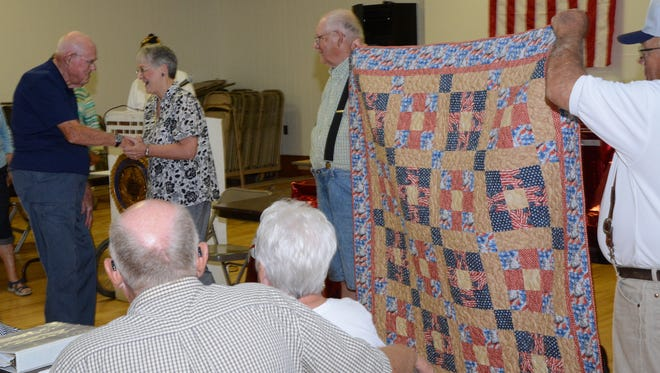 """Pat Ann Hefel, Quilts of Valor Foundation, greets Jim Williamson, a member of Montezuma's American Legion Blakley-Stevens Post 169 as he is presented with a """"Quilt of Valor"""" at a meeting/banquet held at Montezuma's Memorial Hall on Thursday, June 14."""