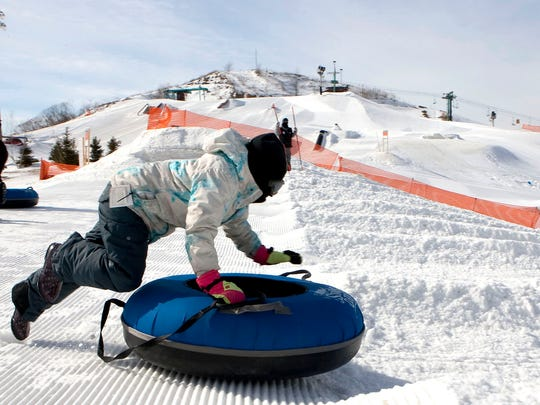 Juliana Eadle, 10, leaps onto her inner tube as she sleds at The Rock Sports Complex during a Franklin Education Foundation snow tubing outing in 2014.