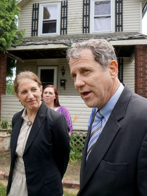 U.S. Department of Health and Human Services Secretary Sylvia Mathews Burwell listens to Sen. Sherrod Brown talk about the value of CHAP in the front of a home of a family that uses the service.