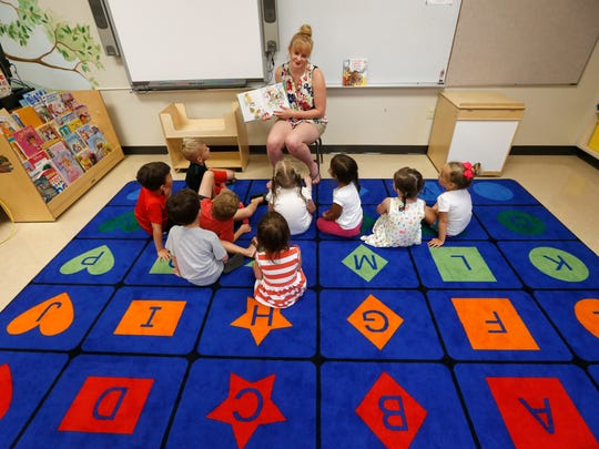 Melany Cronkhite reads a book to her students during